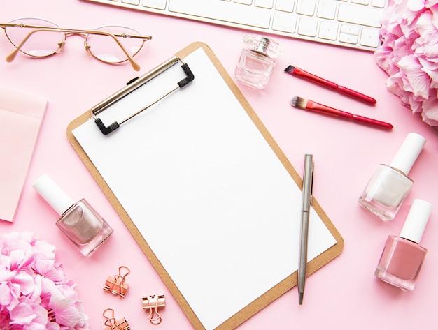 Presse-papiers vierge avec fleurs, maquillage et clavier, vue de dessus