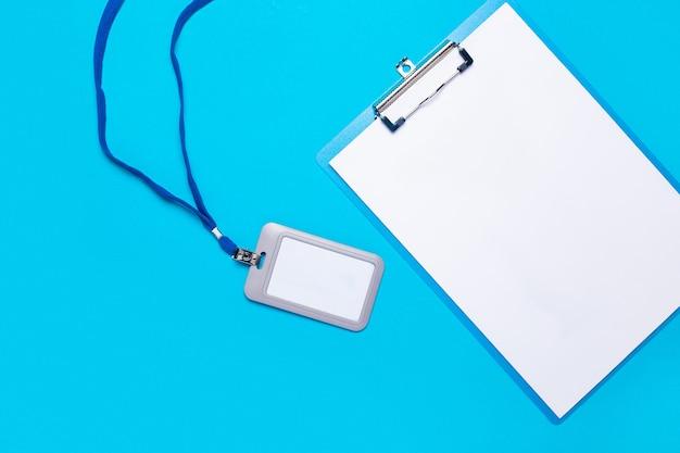 Presse-papiers vierge et insigne nominatif en plastique avec cordon bleu sur surface bleu clair