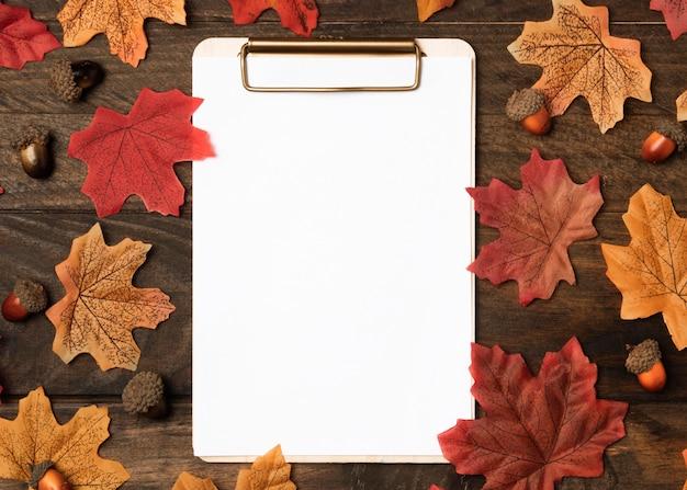 Presse-papiers vue de dessus entouré de feuilles d'automne