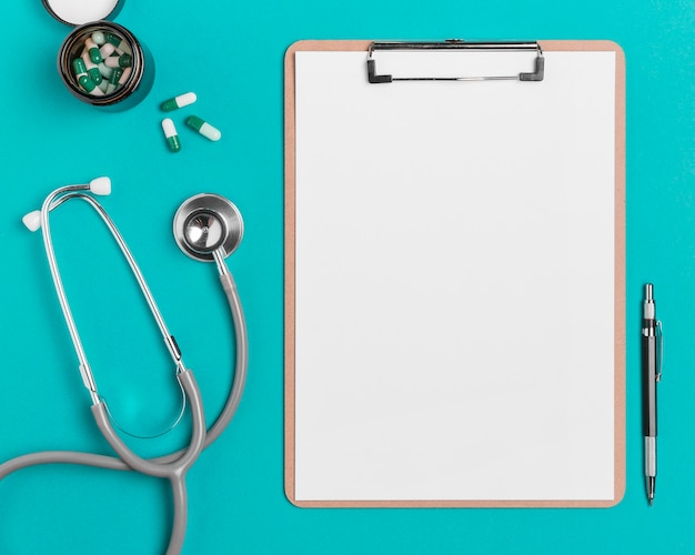 Presse-papiers vue de dessus avec stéthoscope et pilules