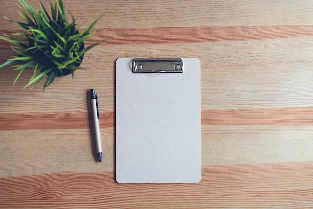 Presse-papiers vue de dessus avec un stylo et du papier blanc sur le fond de la table. se moquer de texte bann