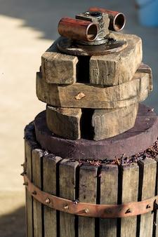 Pressoir à moût rouge et vis hélicoïdale. les mains du vigneron se bouchent.