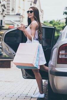 Prêt à acheter plus. belle jeune femme portant des sacs à provisions et souriant tout en se tenant près de la voiture dans la rue