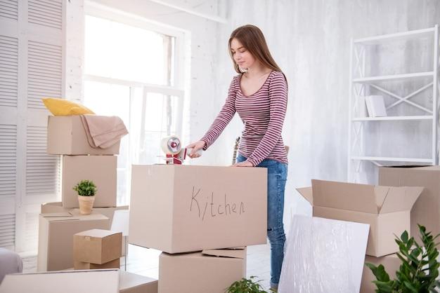 Prêt à bouger. jolie fille aux cheveux noirs qui enregistre la boîte avec des couverts de cuisine tout en emballant ses affaires avant de quitter l'appartement
