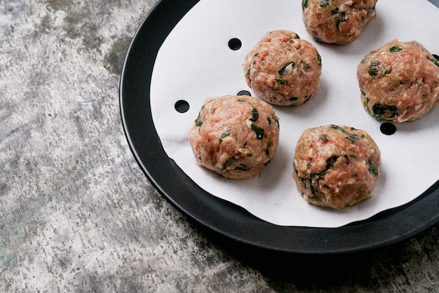 Prêt à cuire les boulettes de viande dans une assiette noire sur du papier sulfurisé, mise au point sélective. fermer