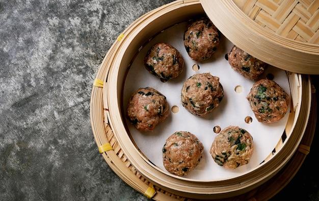 Prêt à cuire des boulettes de viande dans un cuiseur vapeur en bambou asiatique vue de dessus. mise à plat.