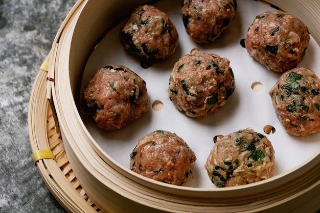 Prêt à cuire des boulettes de viande dans un cuiseur vapeur en bambou asiatique