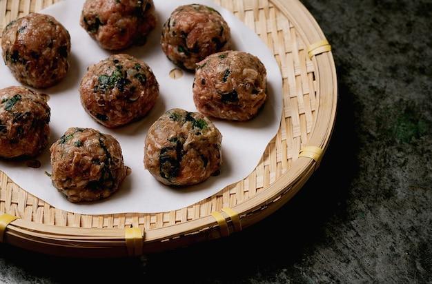 Prêt à cuire des boulettes de viande sur papier sur un plateau en bambou asiatique. fermer