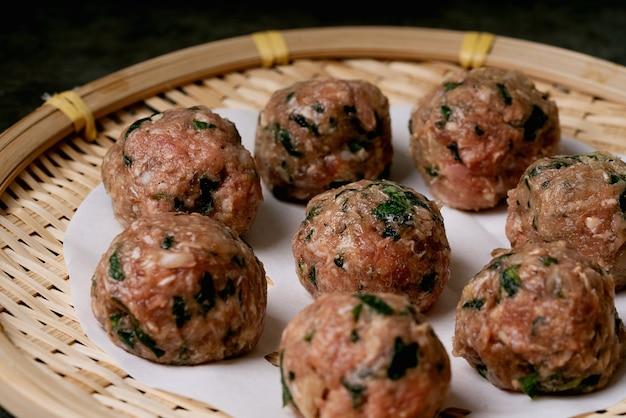 Prêt à cuire des boulettes de viande sur papier sur un plateau en bambou asiatique. mise au point sélective. fermer