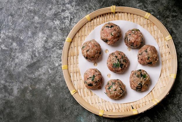 Prêt à cuire des boulettes de viande sur papier sur un plateau en bambou asiatique. vue de dessus. mise à plat.