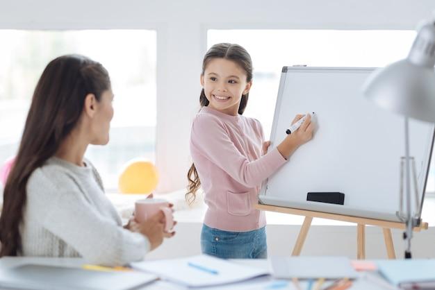 Prêt à écrire. joyeuse fille mignonne positive debout près du tableau blanc et tenant un surligneur tout en étant prêt à écrire