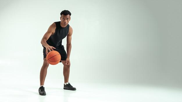 Prêt à gagner toute la longueur du jeune homme africain en vêtements de sport jouant au basket-ball dans