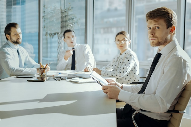 Prêt à gronder. beau jeune manager assis à la réunion avec le conseil d'administration et l'air nerveux, se sentant coupable et réprimandé
