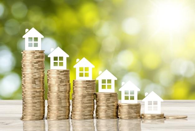Prêt immobilier, hypothèque inversée, concept de refinancement d'actifs : petite maison ou maison sur des piles de pièces,
