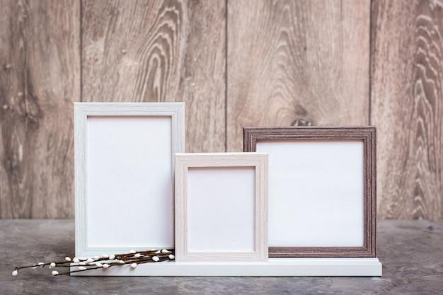 Prêt maquette. trois cadres de photo vides sur le support et des branches de saule artificiel sont sur la table. gamme de couleurs blanc-gris-beige