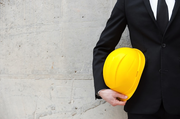 Prêt à nouveau projet. image recadrée d'un homme en tenue de soirée tenant un casque tout en se tenant contre le mur de béton