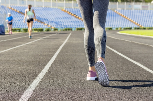 Prêt à partir. gros plan sur la chaussure de l'athlète féminine sur la ligne de départ. fille sur la piste du stade, se préparant pour une course. sport et concept santé