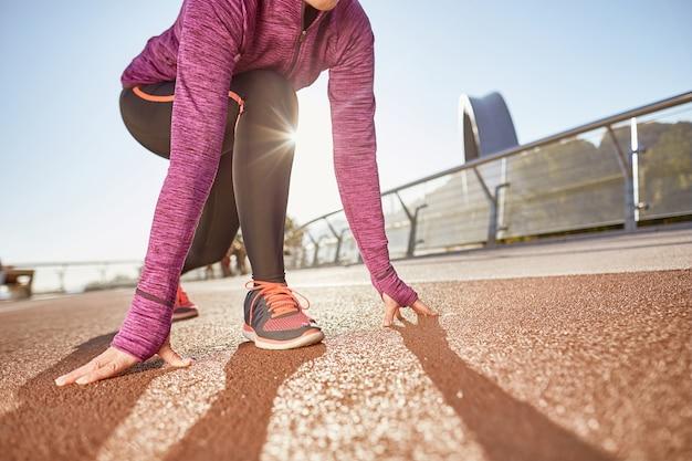 Prêt à partir photo recadrée d'une femme mature active portant des vêtements de sport debout en position de départ prête