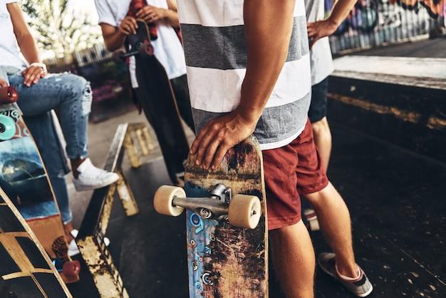 Prêt à patiner. gros plan de jeunes gens modernes debout avec des planches à roulettes tout en passant du temps à l'extérieur