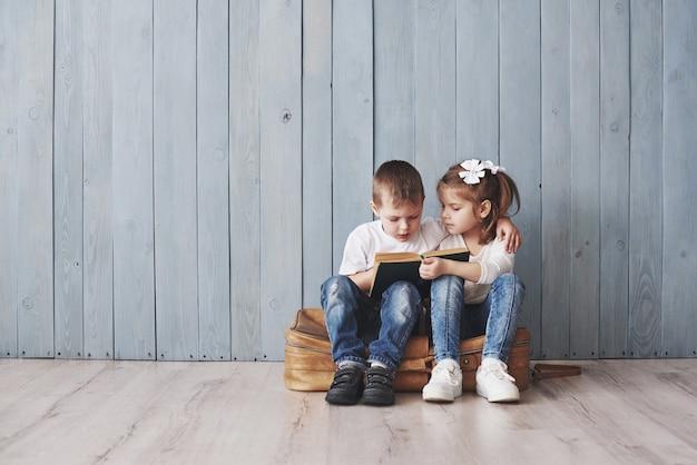 Prêt pour les grands voyages. heureuse petite fille et garçon lisant un livre intéressant portant une grande mallette. concept de liberté et d'imagination