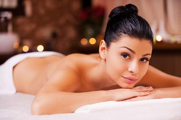 Prêt pour le massage. belle jeune femme torse nu allongée sur la table de massage et regardant la caméra