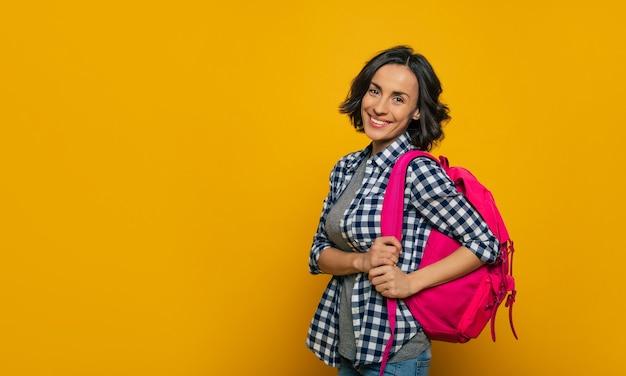 Prêt pour une nouvelle journée dans mon université! une jeune étudiante, habillée avec désinvolture, les épaules tournées sur le côté, souriant et tenant son joli sac à dos rose sur son épaule.