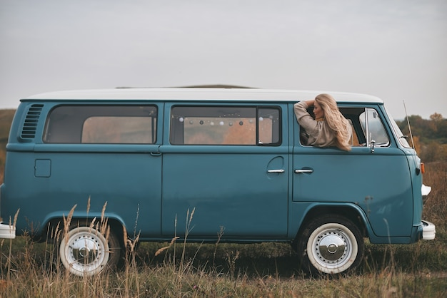 Prêt pour de nouvelles aventures. jolie jeune femme se penchant par la fenêtre de la camionnette tout en profitant du voyage en voiture