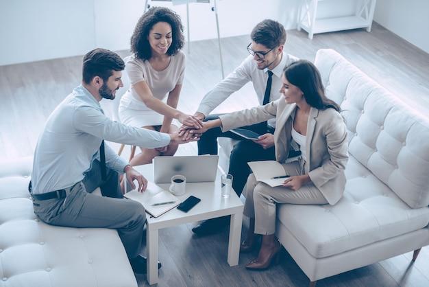 Prêt pour de nouvelles réalisations. vue de dessus d'un groupe de quatre jeunes se tenant la main et montrant leur unité avec le sourire alors qu'ils étaient assis sur le canapé au bureau