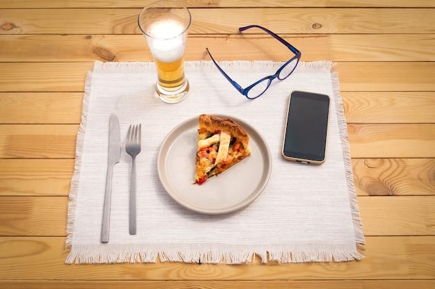 Prêt pour un repas léger. présentation d'une part de tarte végétalienne saine à base de légumes et cuite au four. bien-être et alimentation. verre de bière, lunettes et téléphone portable sur la table en bois.