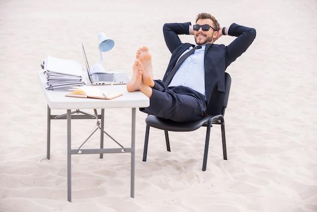 Prêt pour les vacances. beau jeune homme en tenue de soirée et lunettes de soleil tenant les mains derrière la tête et tenant ses pieds sur la table debout sur le sable
