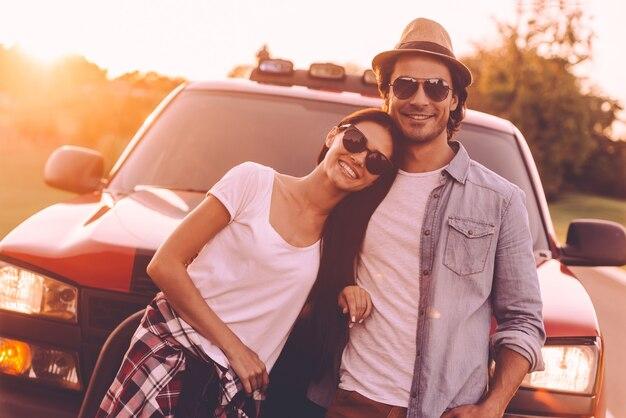 Prêt pour le voyage en voiture. beau jeune couple souriant se liant les uns aux autres et s'appuyant sur leur camionnette
