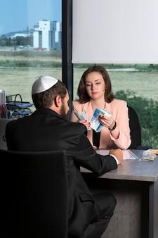 Le prêt sur salaire est en espèces. une femme compte l'argent israélien, le salaire d'un homme juif dans une kippa et un costume en fonction. dame d'affaires remettant de nouvelles factures de shekels. dollars et nouveaux shekels, billets nis sur la table