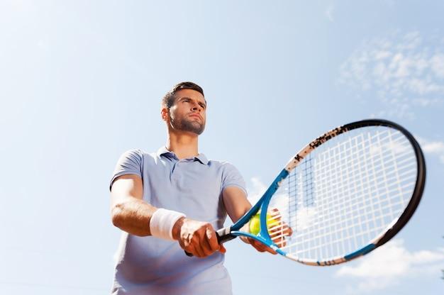 Prêt à servir. vue à faible angle du beau jeune homme en polo tenant une raquette de tennis et une balle en se tenant debout contre le ciel bleu