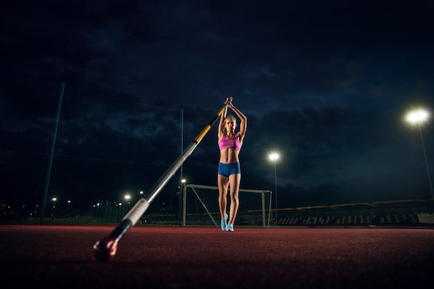 Prêt à surmonter les difficultés. formation professionnelle de saut à la perche féminine au stade le soir. pratiquer à l'extérieur. notion de sport