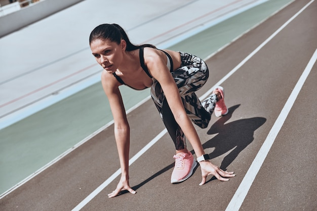 Prêt à surmonter n'importe quel obstacle. belle jeune femme en vêtements de sport debout sur la ligne de départ