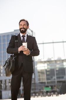 Prêt à travailler. joyeux bel homme d'affaires, boire du café tout en allant travailler