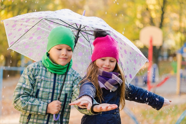 Preteen boy and girl walk in rainy park extérieur