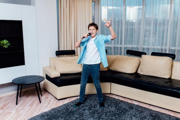 Preteen boy chantant avec microphone dans le salon à la maison.