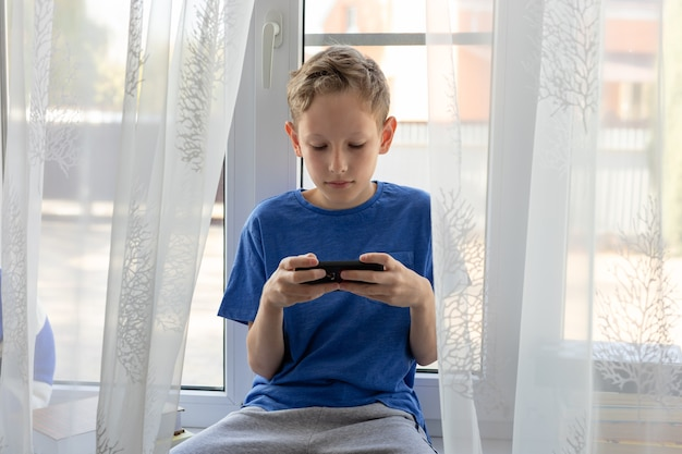 Preteen boy utilise un téléphone mobile, joue, utilise des applications