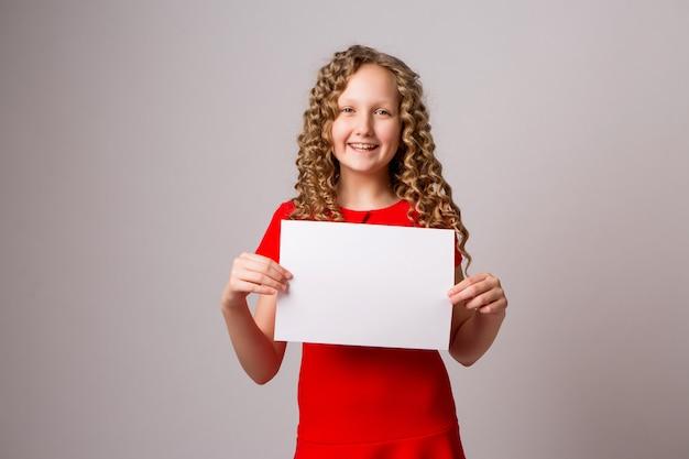 Preteen fille avec une feuille de papier vierge ou une pancarte