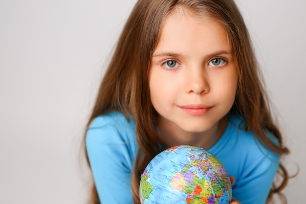 Preteen fille tenant un globe terrestre