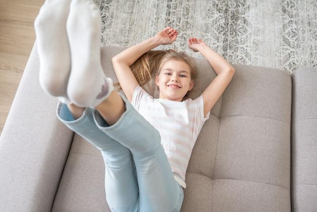 Preteen girl allongé sur le canapé avec ses pieds se levant haut