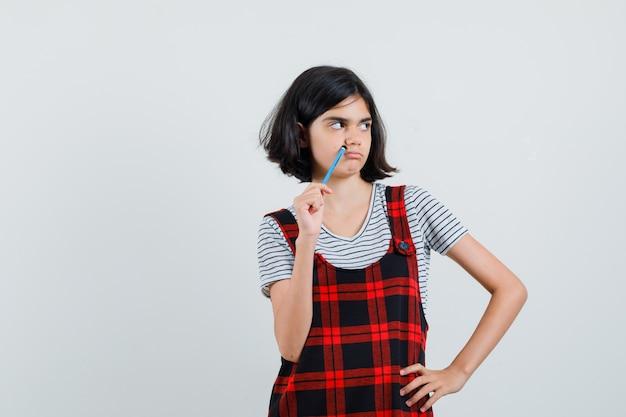 Preteen girl en détournant les yeux tout en tenant un stylo en t-shirt