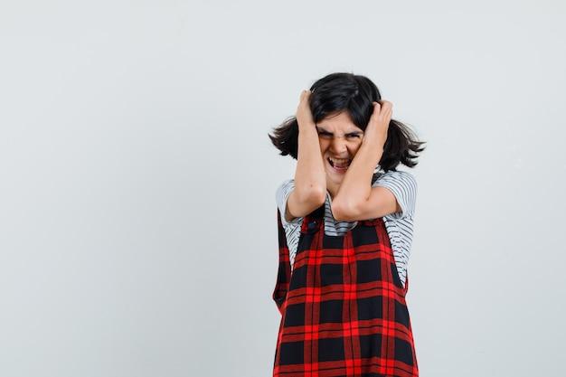 Preteen girl étreignant la tête avec les mains en t-shirt