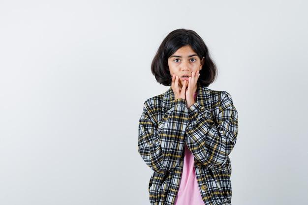 Preteen girl holding hand sur les joues en chemise, veste et à l'air anxieux , vue de face.