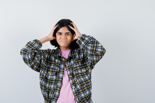 Preteen girl holding hands on head in shirt,veste vue de face.