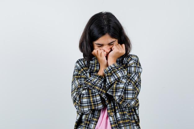 Preteen girl holding poings sur la bouche en chemise, veste et à la colère. vue de face.
