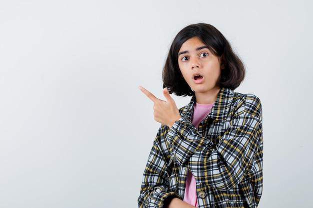 Preteen girl in shirt,veste pointant de côté et l'air surpris, vue de face. espace pour le texte