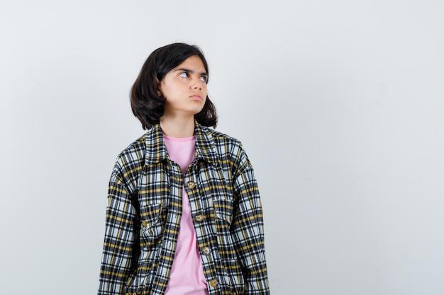 Preteen girl in shirt,veste regardant de côté, vue de face.
