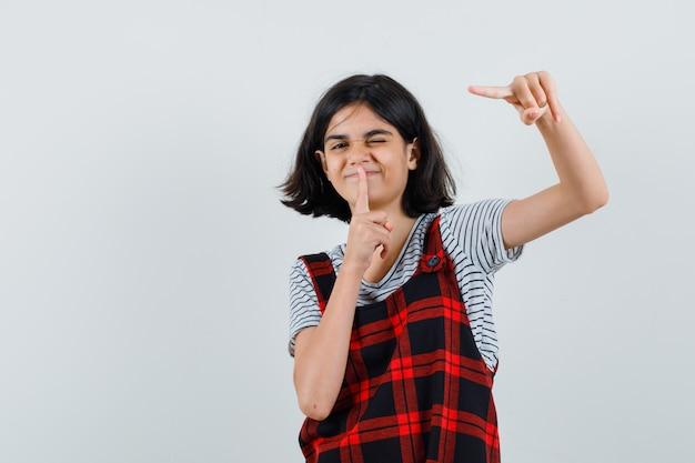 Preteen girl montrant un geste silencieux tout en pointant de côté en t-shirt